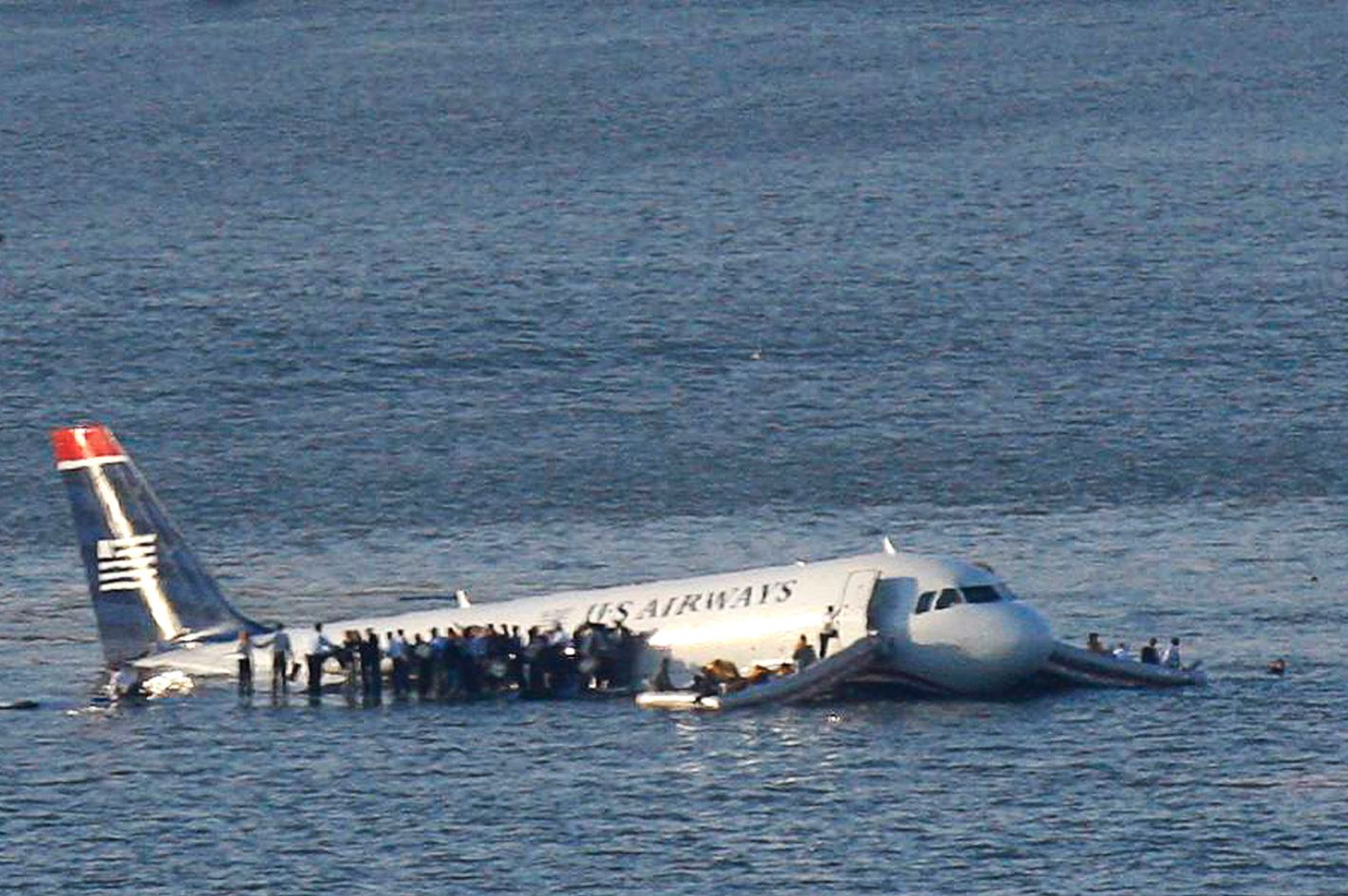 Passengers stand on the wings of a U.S. Airways plane as a ferry pulls up to it after it landed in the Hudson River in New York, January 15, 2009. Local media said the plane was an Airbus with 146 passengers and five crew which had just taken off from La Guardia Airport and was trying to return after apparently striking a flock of birds.