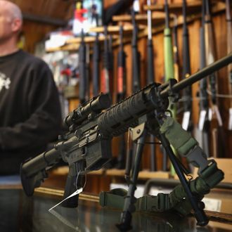 TINLEY PARK, IL - DECEMBER 17: An AR-15 style rifle sits on the counter by Craig Marshall as he assists a customer at Freddie Bear Sports sporting goods store on December 17, 2012 in Tinley Park, Illinois. Americans purchased a record number of guns in 2012 and gun makers have reported a record high in demand. Firearm sales have surged recently as speculation of stricter gun laws and a re-instatement of the assault weapons ban following the mass school shooting in Connecticut . (Photo by Scott Olson/Getty Images)