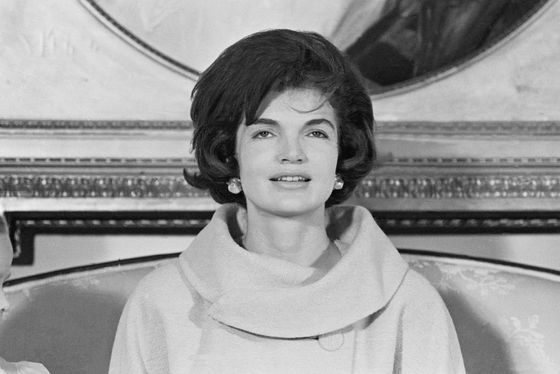 "In her nationally syndicated ""Campaign Wife"" column, Jacqueline Kennedy asked:  ""What does my hairdo have to do with my husband's ability to be President?"" Nothing and everything as it turns out. While her hair had little to do with JFK's political acumen, Jackie's style visually reinforced the administration's youthful vitality and forward-thinking agenda. Tended by Kenneth Battelle, Jackie's bouffant was set on Lucite rollers to achieve a lifted ""Italian Cut"" look. And while she abhorred hats, she bowed to formal protocol and the milliner's union by wearing pillboxes by Halston. Tambourin styles had been in vogue since the thirties, but eager to preserve her coif and bare her face, Jackie took to tilting hers at the crown."