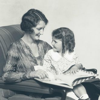 18 May 1927 --- Mother & daughter smiling sitting in chair reading book.