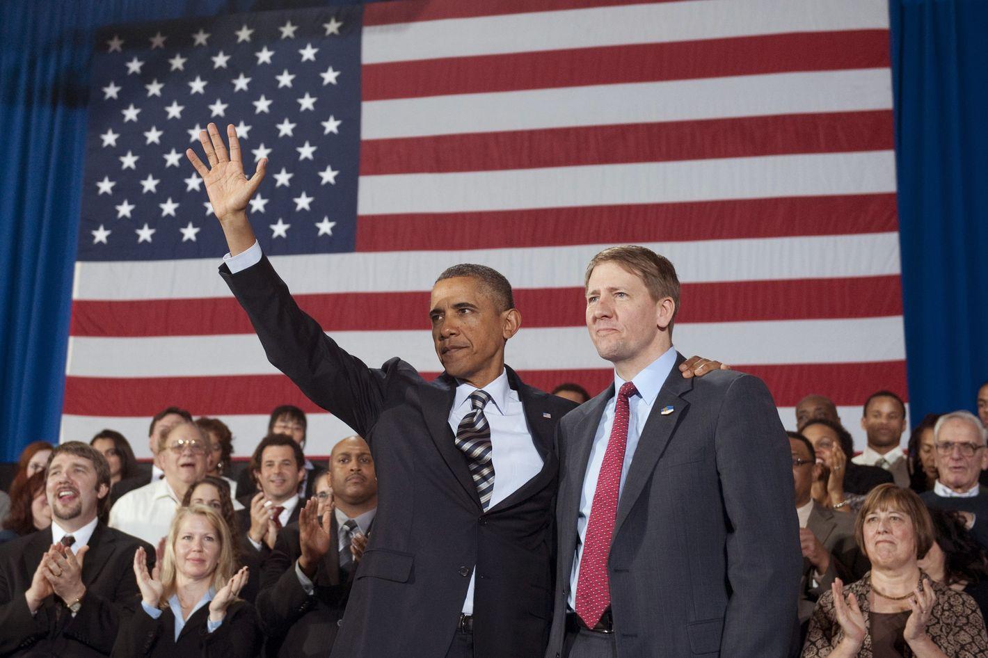 US President Barack Obama waves alongside Richard Cordray (R) on January 4, 2012.