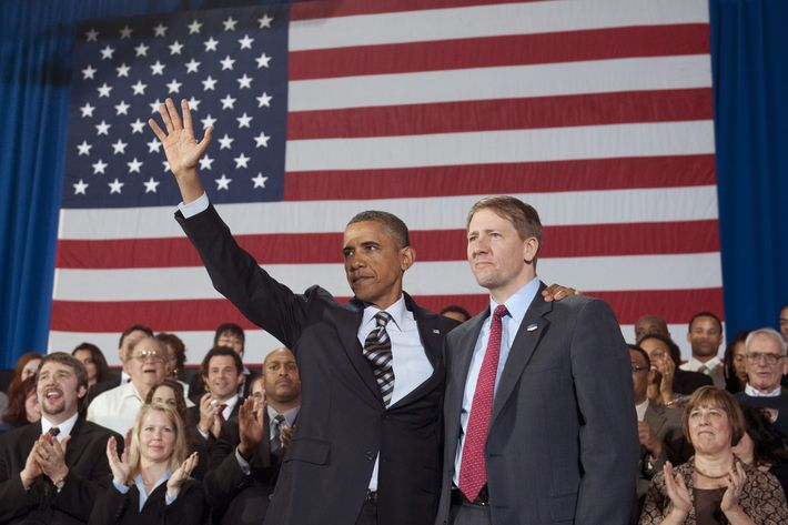 US President Barack Obama waves alongside Richard Cordray (R) on January 4, 2012.