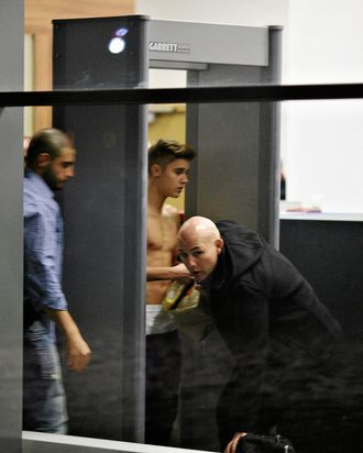 Image #: 21764087 Bodyguards try to block the view of Canadian singer Justin Bieber as he goes through Wladyslaw Reymont Airport in Lodz following his concert March 25, 2013. REUTERS/Tomasz Stanczak/Agencja Gazeta (POLAND - Tags: ENTERTAINMENT PROFILE) REUTERS /AGENCJA GAZETA /LANDOV