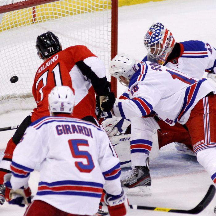 Ottawa Senators' Nick Foligno (71) scores on New York Rangers goaltender Martin Biron as Rangers' Dan Girardi and Marc Staal, defend during first period NHL hockey action in Ottawa, Ontario, on Thursday March 8, 2012.