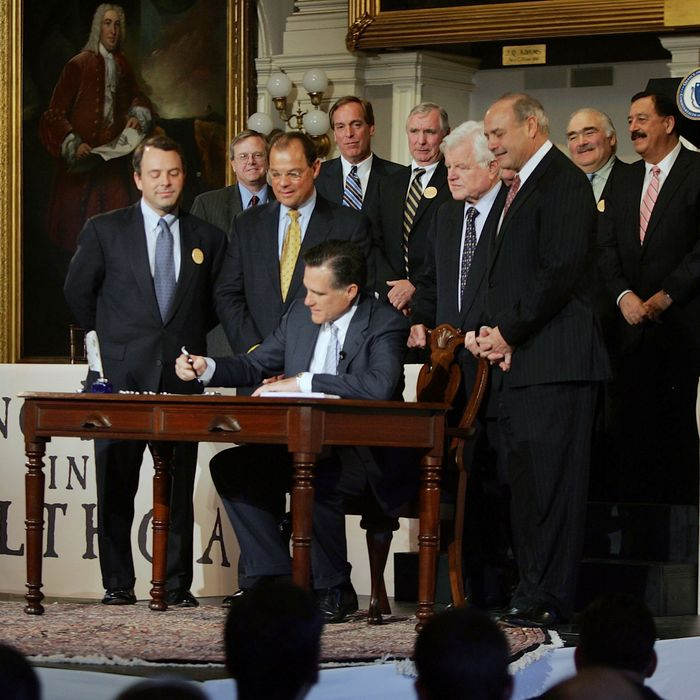 BOSTON - APRIL 12: Massachusetts Governor Mitt Romney signs into law a new health care reform bill during a ceremony at Faneuil Hall April 12, 2006 in Boston, Massachusetts. U.S. Sen. Edward Kennedy (D-MA) (2nd R) and others joined Romney for the signing of the bill, which makes Massachusetts the first state in the country to require that all residents have health insurance. (Photo by Joe Raedle/Getty Images)