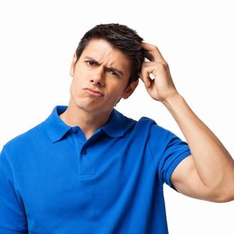Portrait of confused young man in a casual blue t-shirt scratching his head. Horizontal shot. Isolated on white.
