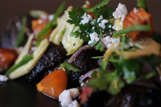 Anise-marinated hanger steak with shaved artichokes, persimmons, lovage, feta and chili.