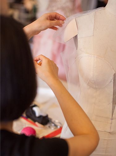 Woman pinning paper mock to dress form shoulder
