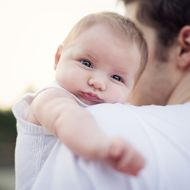 Cute Baby looking over Daddy's Shoulder
