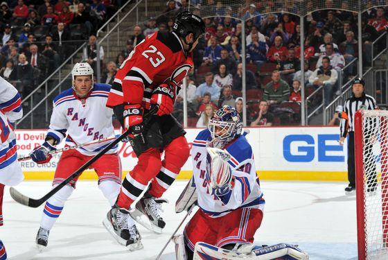 NEWARK, NJ - MARCH 06:  David Clarkson #23 of the New Jersey Devils leaps in front of Henrik Lundqvist #30 of the New York Rangers during the second period on March 6, 2012 at the Prudential Center in Newark, New Jersey. (Photo by Christopher Pasatieri/Getty Images)