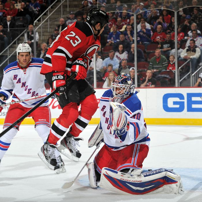 David Clarkson #23 of the New Jersey Devils leaps in front of Henrik Lundqvist #30 of the New York Rangers