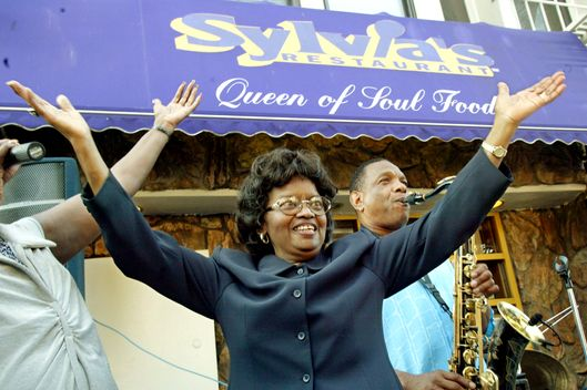 "In this Aug. 1, 2002 file photo, Sylvia Woods, center, moves to the music outside her restaurant, ""Sylvia's,"" during the restaurant's 40th anniversary celebration, in the Harlem neighborhood of New York. Woods died in Mount Vernon, N.Y. on Thursday, July 19, 2012. She was 86."