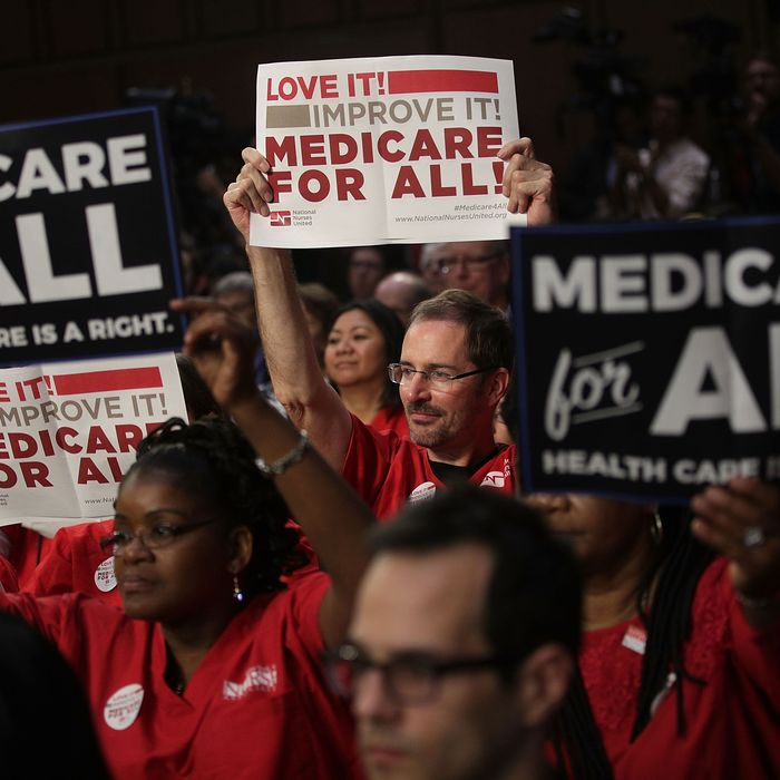 Supporters of U.S. Sen. Bernie Sanders hold signs during an event to introduce the Medicare for All Act of 2017.