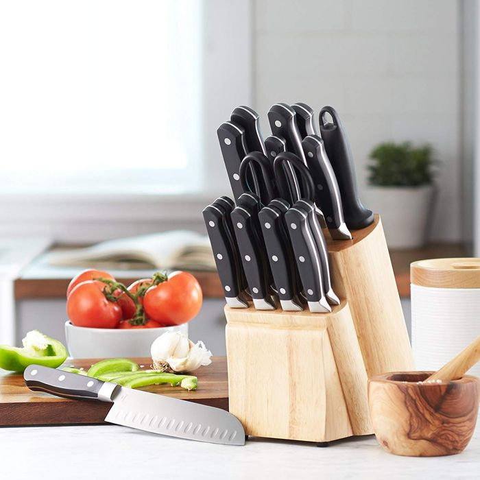 wooden knife set next to a cutting board with tomatoes, garlic, and peppers - strategist best kitchen knife sets