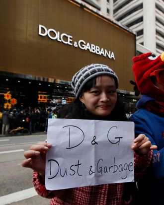 Protesters hold a placard outside a chain store of Dolce & Gabbana in Hong Kong Sunday, Jan. 8, 2012. Hundreds of Hong Kong protesters staged a protest outside an Italian luxury clothing chain store Dolce & Gabbana to demand an apology from the chain for allegedly preventing locals from taking photos of its storefront display. One of the security guards had earlier been reported as saying that only Mainland shoppers were allowed to take pictures of the store, even at the public road outside.