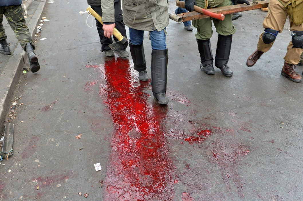 Anti-government protesters walk on a puddle of blood left by a wounded demonstrator during clashes with the police in the center of Kiev on February 20, 2014.  Armed protesters stormed police barricades in Kiev on Thursday in renewed violence that killed at least 26 people and shattered an hours-old truce as EU envoys held crisis talks with Ukraine's embattled president. Bodies of anti-government demonstrators lay amid smouldering debris after masked protesters hurling Molotov cocktails and stones forced police from Kiev's iconic Independence Square -- the epicentre of the ex-Soviet country's three-month-old crisis. AFP PHOTO/ SERGEI SUPINSKY        (Photo credit should read SERGEI SUPINSKY/AFP/Getty Images)