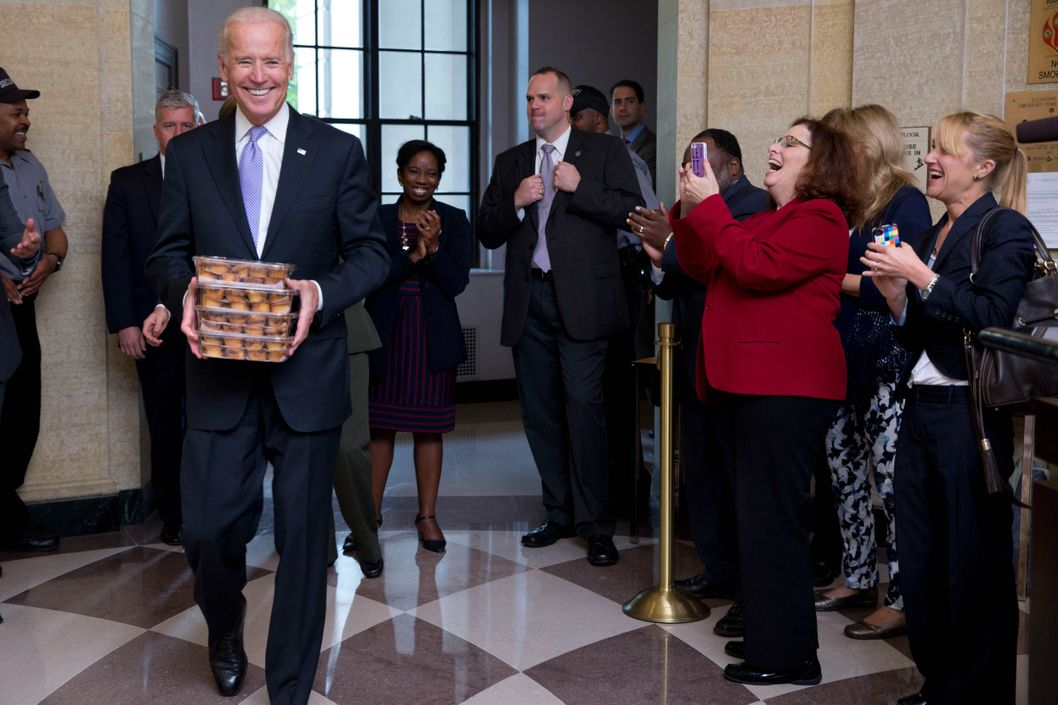 Vice President Joe Biden, left, greets Environmental Protection Agency workers with muffins as they return to work after 16 days of a government shutdown at the William Jefferson Clinton Federal Building in Washington on Thursday, Oct. 17, 2013.  After 16 days of being off the job, thousands of furloughed federal workers are returning to work now that the government shutdown has been resolved.
