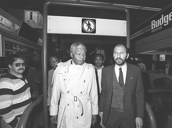 On his first official visit to Cape Town following his release, Nelson Mandela (left) is accompanied by Trevor Manuel, then head of the ANC's Department of Economic Planning at the then DF Malan airport in Cape Town. On the right is anti-Apartheid activist Reggie September. Circa 1990.