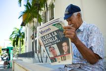 "SAN JUAN, PUERTO RICO - MARCH 14:  Carlos Diaz, 84, reads local newspaper ""El Vocero"" with a front page depicting both Mitt Romney and Rick Santorum and a headline reading, ""The National Battle Arrives on the Island,"" as Republican presidential candidate, former U.S. Sen. Rick Santorum visits La Fortaleza, the governor's mansion, to meet with Governor Luis Fortuno, March 14, 2012 in Old San Juan, Puerto Rico.  Santorum was to meet with Fortuno while on his two-day campaign trip on the island commonwealth. There are 23 GOP delegates up for grabs although Fortuno, a Republican, has already expressed his support for Mitt Romney.   (Photo by Christopher Gregory/Getty Images)"
