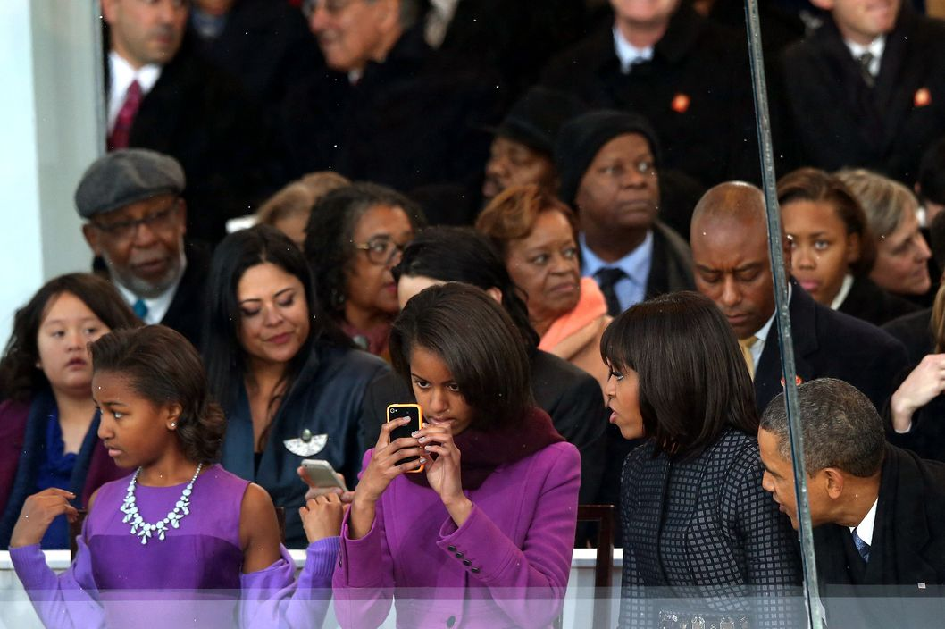 (L-R) Sasha Obama, Malia Obama, first lady Michelle Obama and U.S. President Barack Obama watch from the reviewing stand as the presidential inaugural parade winds through the nation's capital January 21, 2013 in Washington, DC. Barack Obama was ceremonially sworn in for a second term as President of the United States.