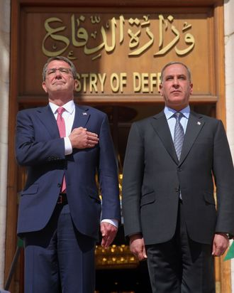 Visiting U.S. Defense Secretary Ash Carter, left, and his Iraqi counterpart Khaled al-Obeidi stand for their country's national anthems during a welcome ceremony at the Ministry of Defense, Baghdad, Iraq, Monday, April 18, 2016. (AP Photo)