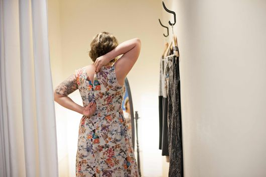 Young woman trying on dress in changing room --- Image by ? Helen King/Corbis