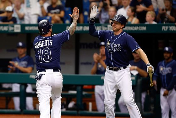 ST. PETERSBURG - SEPTEMBER 03:  Infielder Ryan Roberts #19 of the Tampa Bay Rays is congratulated by Elliot Johnson #9 after scoring the winning run against the New York Yankees during the game at Tropicana Field on September 3, 2012 in St. Petersburg, Florida.  (Photo by J. Meric/Getty Images)