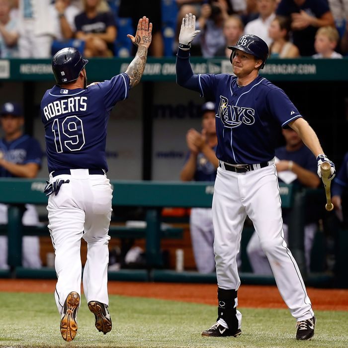 Infielder Ryan Roberts #19 of the Tampa Bay Rays is congratulated by Elliot Johnson #9 after scoring the winning run against the New York Yankees during the game at Tropicana Field on September 3, 2012 in St. Petersburg, Florida.