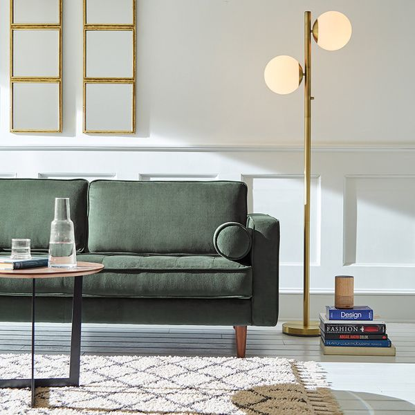 A brass Wayfair floorlamp with two light orbs next to a green couch, a stack of books, and a white and brown patterned rug. The Strategist - Very Tasteful Lamps from Amazon's Rivet and Stone and Beam Are on Sale