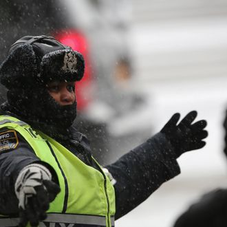 NEW YORK, NY - JANUARY 21: A police officer directs traffic at Union Square during a snowstorm on January 21, 2014 in New York City. Areas of the Northeast are predicted to receive up to a foot of snow in what may be the biggest snowfall of the season so far. (Photo by John Moore/Getty Images)