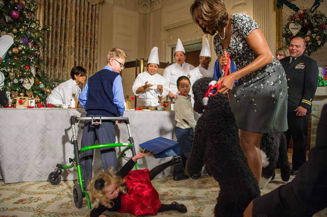 US First Lady Michelle Obama (R) pulls on her dog Sunny as two-year-old Ashtyn Gardner takes a tumble during the White House Christmas decorations viewing at the White House in Washington, DC, December 4, 2013.