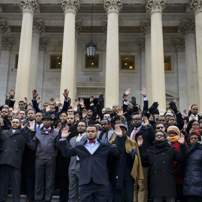 African-American Congressional staff and others hold their hands up during a walk-out outside the House of Representatives on Capitol Hill on December 11, 2014 in Washington, DC. Congressional staff members and others stood outside the Capitol to protest the Eric Garner and Mike Brown grand jury decisions which did not bring charges against police.