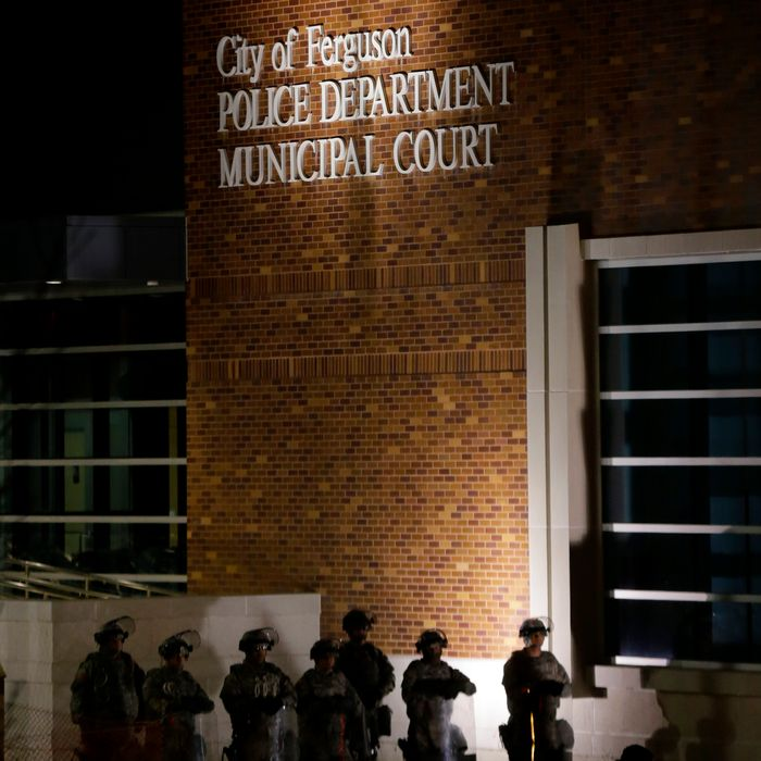 Guardsmen stand in front the Ferguson Police Department Municipal Court bulding, Tuesday, Nov. 25, 2014, in Ferguson, Mo. Missouri's governor ordered hundreds more state militia into the St. Louis suburb, Ferguson, Tuesday after a night of protests and rioting over a grand jury decision's not to indict police officer Darren Wilson in the killing of Michael Brown, a case that has inflamed racial tensions in the U.S. (AP Photo/Charlie Riedel)