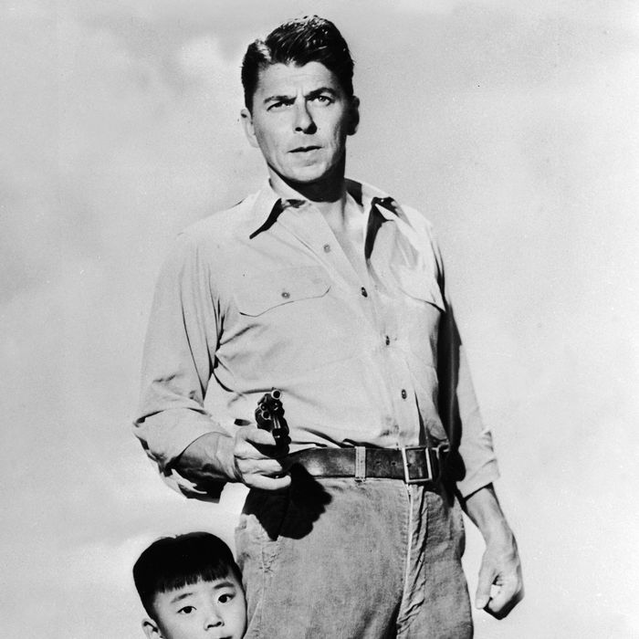 Chinese child actor Danny Chang clings to the leg of American actor and politician Ronald Reagan (1911 - 2004) in a publicity still for the feature film 'Hong Kong' directed by Lewis R. Foster, 1951.