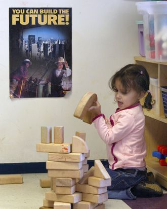 A young girl participates in a child-initiated activity as she attempts to construct a building with blocks February 13, 2004 at the Erie Neighborhood House in Chicago.