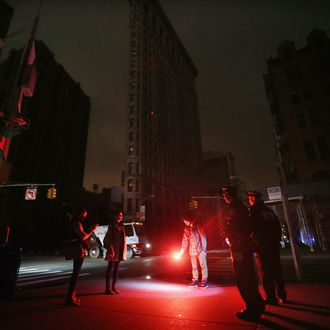 Police gather to tell a man to put out the road flare he found and was using as an impromptu flashlight while walking with friends in front of a darkened Flatiron Building in a section of Manhattan still in a blackout following Hurricane Sandy on October 30, 2012 in New York City. The storm has claimed at least 40 lives in the United States, and has caused massive flooding across much of the Atlantic seaboard. US President Barack Obama has declared the situation a 'major disaster' for large areas of the US East Coast including New York City. NEW YORK, NY - OCTOBER 30: Police gather to tell a man to put out the road flare he found and was using as an impromptu flashlight while walking with friends in front of a darkened Flatiron Building in a section of Manhattan still in a blackout following Hurricane Sandy on October 30, 2012 in New York City. The storm has claimed at least 40 lives in the United States, and has caused massive flooding across much of the Atlantic seaboard. US President Barack Obama has declared the situation a 'major disaster' for large areas of the US East Coast including New York City. (Photo by Mario Tama/Getty Images)