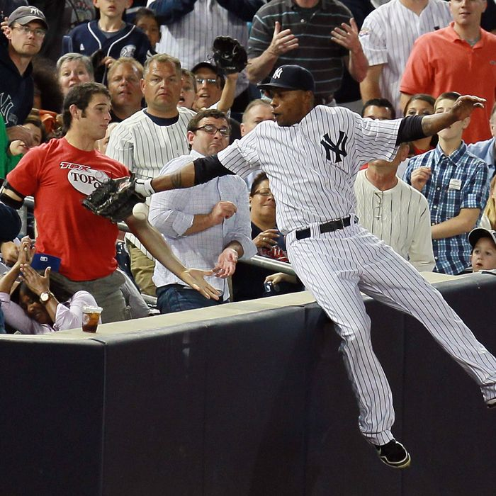 Dewayne Wise #45 of the New York Yankees falls into the stands after making a catch off the bat of Jack Hannahan #9 of the Cleveland Indians in the seventh-inning at Yankee Stadium on June 26, 2012.
