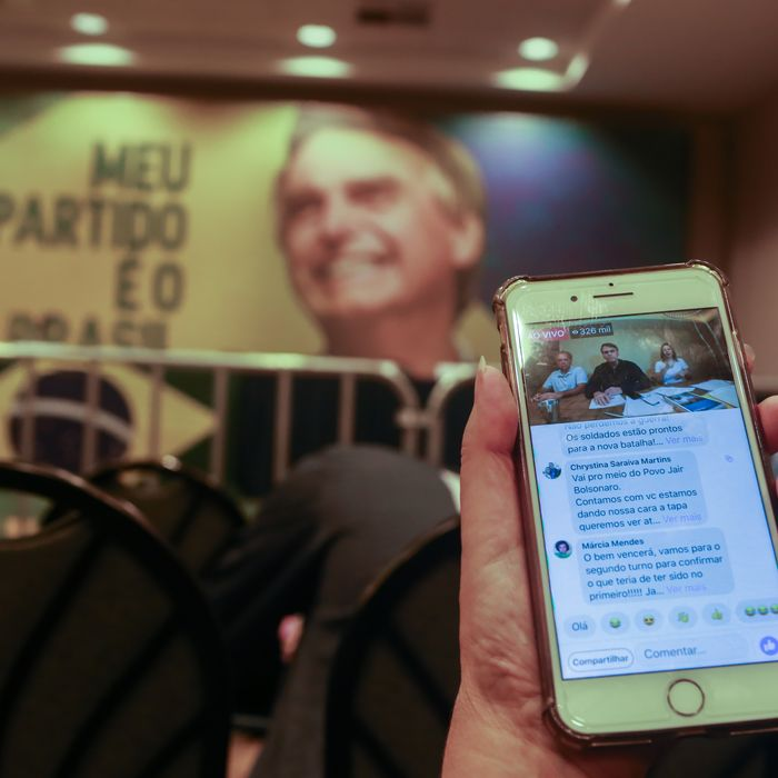 On a smartphone, journalists watch Jair Bolsonaro, an extreme right-wing presidential candidate, speak live about the results of the first round of the election.