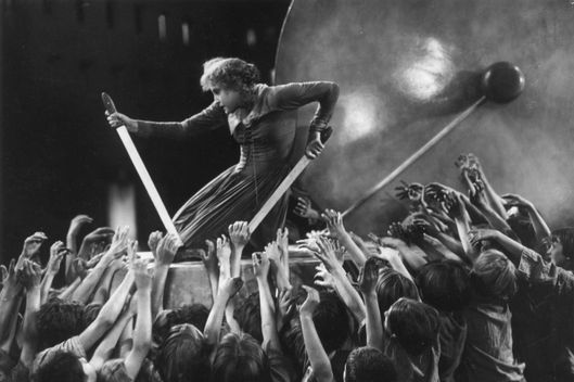 1927:  German actress Brigitte Helm (1906 - 1996) operates the controls amidst a crowd of desperate children in the UFA film 'Metropolis', directed by Fritz Lang.  (Photo by Hulton Archive/Getty Images)