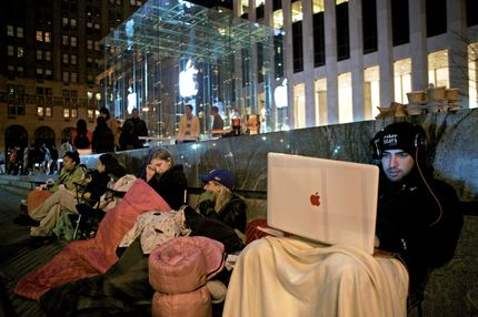 NEW YORK - APRIL 2:  Sinai Azmoudea, 23, of Dallas Texas, right, waits on line for the release of Apple's iPad on April 2, 2010 at the Apple Store on Fifth Avenue in New York City. Employees set up barriers to control the throngs expected to line up for the $499 device which goes on sale Saturday. (Photo by David Goldman/Getty Images)