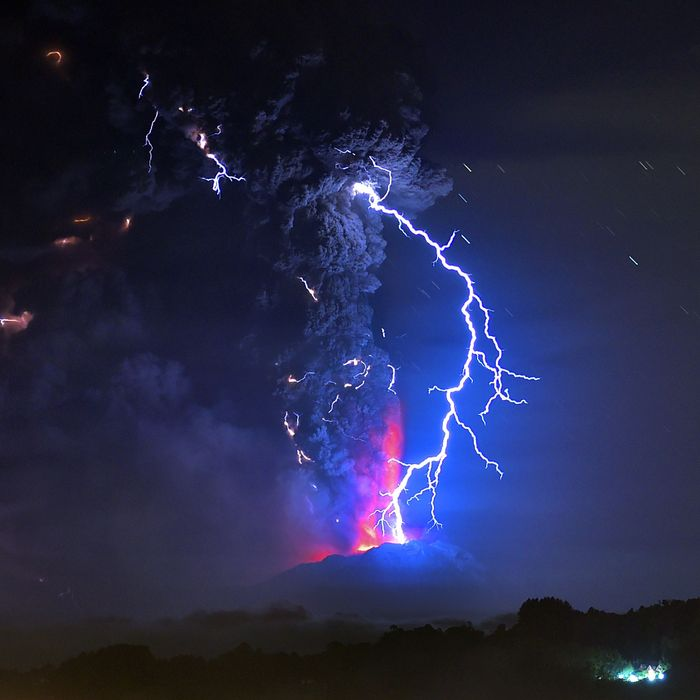 View from Frutillar, southern Chile, showing volcanic lightnings and lava spewed from the Calbuco volcano on April 23, 2015. Chile's Calbuco volcano erupted on Wednesday, spewing a giant funnel of ash high into the sky near the southern port city of Puerto Montt and triggering a red alert. Authorities ordered an evacuation for a 10-kilometer (six-mile) radius around the volcano, which is the second in southern Chile to have a substantial eruption since March 3, when the Villarrica volcano emitted a brief but fiery burst of ash and lava. AFP PHOTO/MARTIN BERNETTI (Photo credit should read MARTIN BERNETTI/AFP/Getty Images)