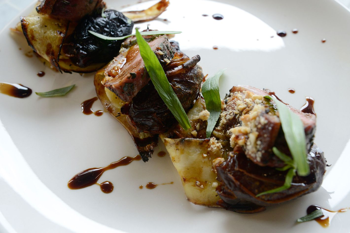 Duck with 'nduja-stuffed dates, parsnips, hazelnuts, and pekmez (Turkish fruit-must syrup).