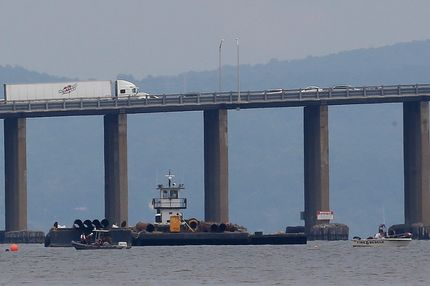 Rescue workers on boats search near a construction barge on the Hudson River in Piermont, N.Y. on Saturday, July 27, 2013, south of the Tappan Zee Bridge for two people who are believed to have fallen into the water during a boat crash. Two people are missing and four others are injured after their boat struck the barge, center, according to the Coast Guard. (AP Photo/Julio Cortez)