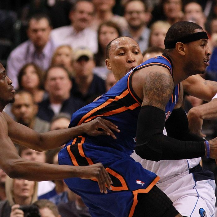 Carmelo Anthony #7 of the New York Knicks dribbles the ball against Shawn Marion #0 and Rodrigue Beaubois #3 of the Dallas Mavericks