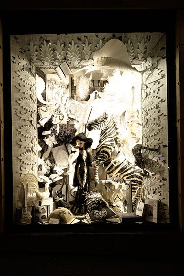 "The ""Teacher's Pets""<b> </b>window is made up of paper products and represents a classroom filled with animals, including a life-size paper zebra, ostrich, panda bear, aardvark, white peacock, and more. The ""students"" are surrounded by zoological textbooks, and the teacher wears a black-and-white lace Marchesa gown."
