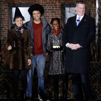Bill de Blasio, right, laughs with his family, Chiara de Blasio, left, Dante de Blasio, second from left, and Chirlane McCray before being sworn in as the mayor of New York City at the start of the new year, Wednesday, Jan. 1, 2014 in New York. De Blasio took the oath of office moments after midnight at his home in Park Slope, Brooklyn. His inauguration will be celebrated at noon Wednesday, January 1, 2014 on the steps of City Hall when he takes the oath again, which will be administered by former US president Bill Clinton.