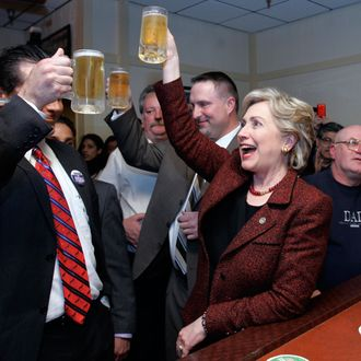 12 Apr 2008, USA --- Democratic presidential hopeful, Sen. Hillary Rodham Clinton, D-N.Y., raises her mug of beer in a toast with Hammond, Ind., Mayor Tom McDermott, left, as she stops at the bar during a campaign stop at Bronko's restaurant in Crown Point, Ind., Saturday, April 12, 2008.