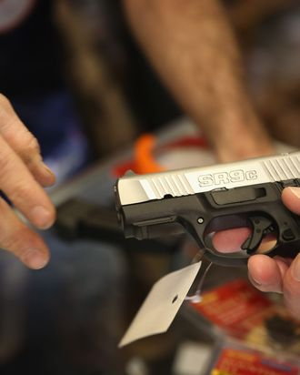 TINLEY PARK, IL - DECEMBER 17: A customer shops for a pistol at Freddie Bear Sports sporting goods store on December 17, 2012 in Tinley Park, Illinois. Americans purchased a record number of guns of guns in 2012. Gun sales have surged recently with people buy guns for personal protection following the mass shooting in Connecticut and gun enthusiasts buying guns because they fear a reinstatement of the assault weapons ban. About 47 percent of Americans own guns. (Photo by Scott Olson/Getty Images)