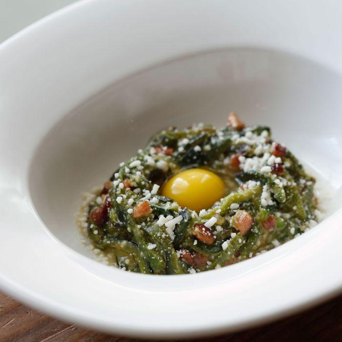 Poblano-pepper carbonara with quail egg, Pecorino cheese, and bacon.