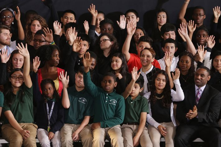 Students raise their hands when asked if they plan on going to college before the arrival of U.S. President Barack Obama at Buck Lodge Middle School February 4, 2014 in Adelphi, Maryland.